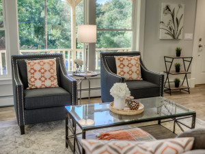 A pop of orange as the accent color dances throughout the living room staging of 776 Jackson Avenue, New Windsor by Claudia Jacobs Designs. Photo credit: Steve Belner, Photovisions