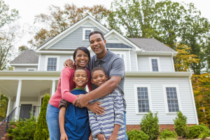 A family of four standing in front of their home they just bought, happy and excited to start a new chapter.
