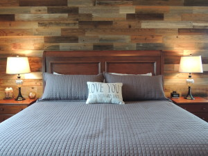 Bedroom with reclaimed wood wall, and grey bed