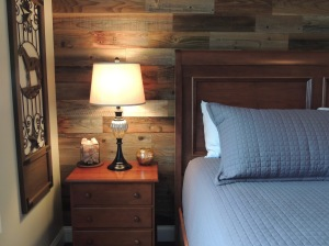 Master bedroom with reclaimed wood accent wall and grey bed