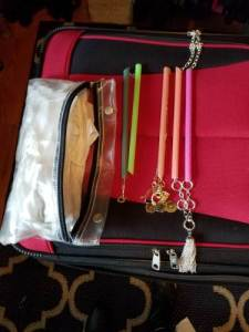 Necklaces in plastic straws to prevent them from getting tangled during travel. On top of a red suitcase with a clear plastic bag next to the necklaces