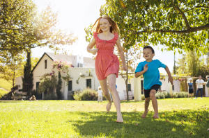 Keeping the house cool during the summer with or without air conditioning by keeping shades down and other cost effective ideas. Kids running in the backyard of a nice house.