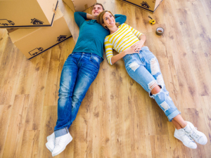 couple laying on the floor with moving boxes