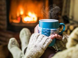 person with sweater with a hot beverage infront of a fireplace.