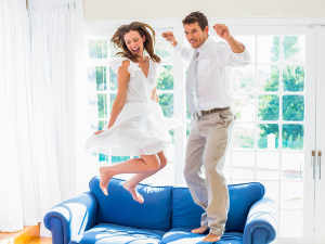 Women and man jumping up off their blue couch