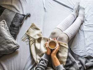 women cozy in bed with a mug of coffee.