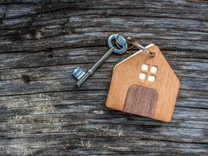 A key with a house keychain on it sitting on wood