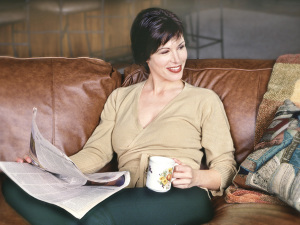 A woman on the couch holding a cup of coffee and the newspaper looking to the right