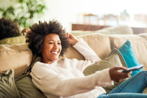 Women on a couch watching tv with the remote in her hand