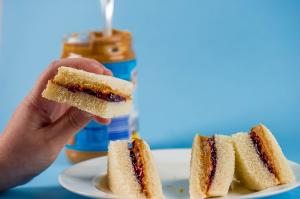 A hand holding a slice of a PB & J Sandwich