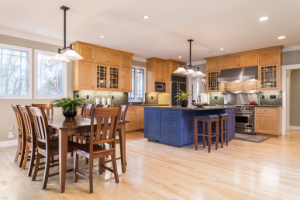 A kitchen that has wooden cabinets and a blue island and a dinning room set
